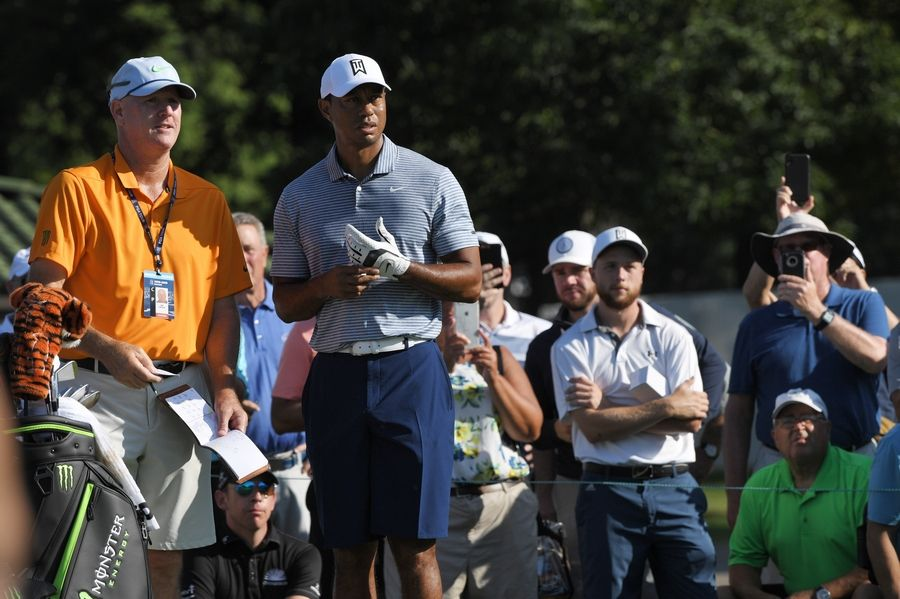 Tiger Woods and caddie Joe LaCava look down the fairway as he prepares to hit his tee shot during the BMW Championship pro-am at Medinah.