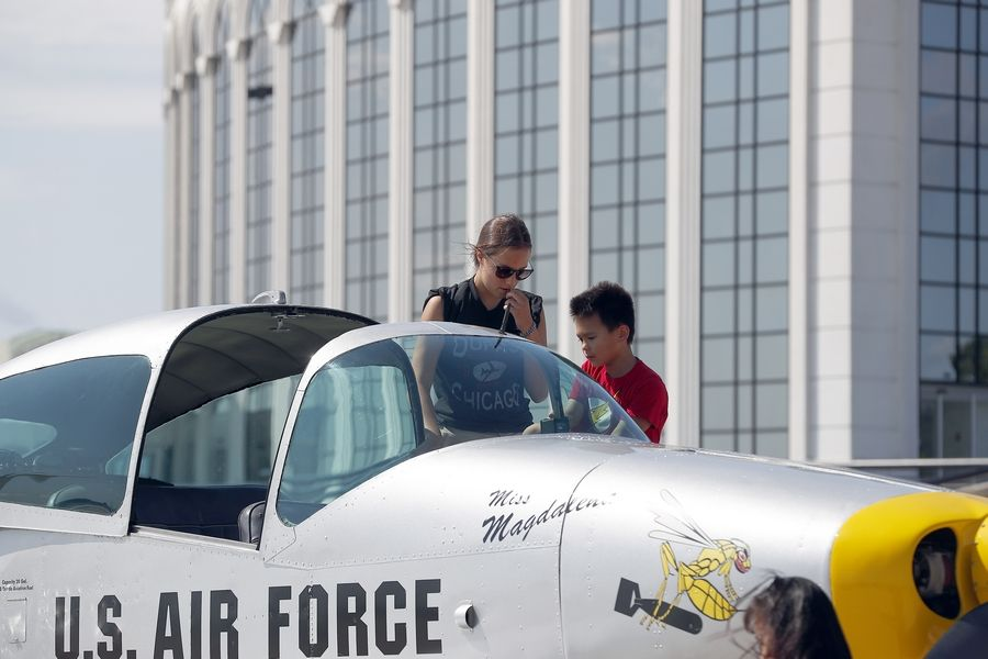 Eight-year-old Caleb Pack of Glendale Heights gets help climbing into a plane from Magdalena Vonic of Hampshire during the third annual DuPage Airport Back to School Celebration.