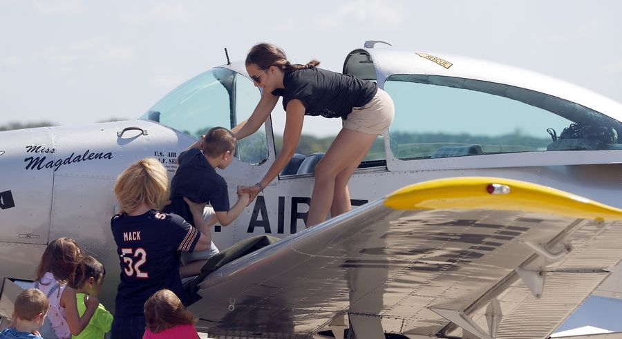 Magdalena Vonic of Hampshire helps a child up to inspect a plane.