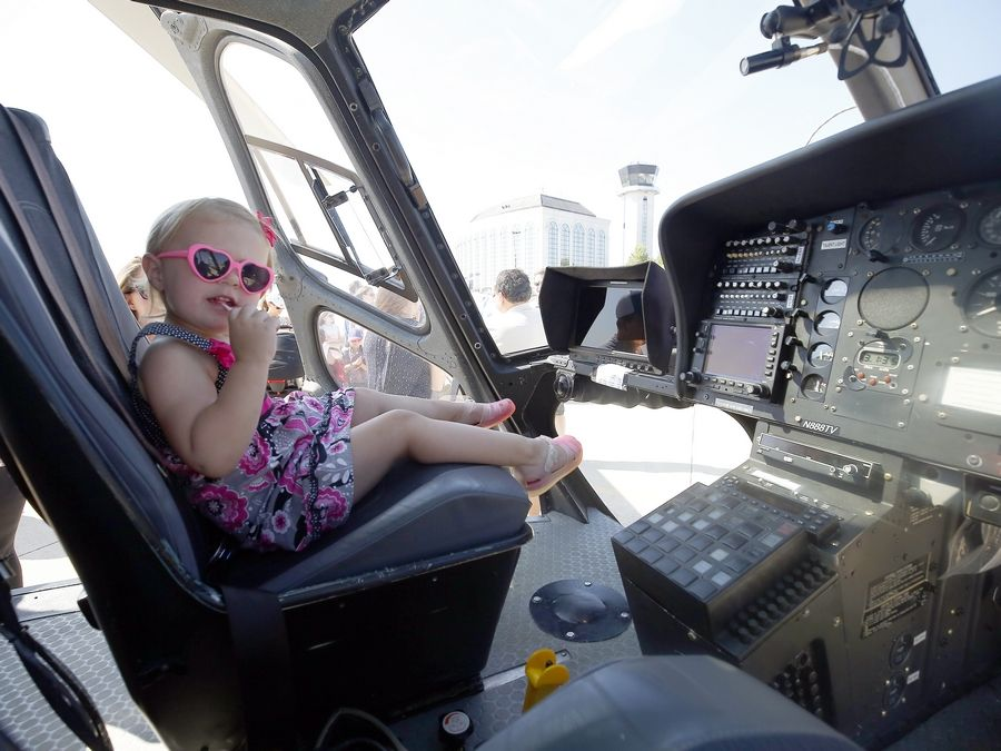 Two-year-old Adeline Duffie of Glen Ellyn checks out the cockpit of the WGN-TV Skycam helicopter. Kids also got to explore fire and rescue vehicles; climb on maintenance and snow removal equipment; experience flight simulators; and see vintage aircraft and military planes.
