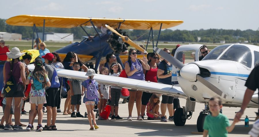 Participants in the DuPage Airport Back to School Celebration view some of the planes along the tarmac.
