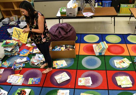New kindergarten teacher Laura Pellegrino sorts books as she sets up her classroom at the Round Lake Unit District 116 Pleviak Kindergarten Center in Lake Villa. The district lowered kindergarten class sizes and hired more teachers with some of the $5.3 million it received in additional state funding.
