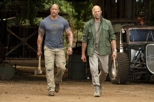"Dwayne Johnson, left, and Jason Statham in ""Fast & Furious Presents: Hobbs & Shaw.""  Movie going audiences have helped the ""Fast & Furious"" spinoff  take another lap at No. 1 even with the onslaught of new movies this weekend."