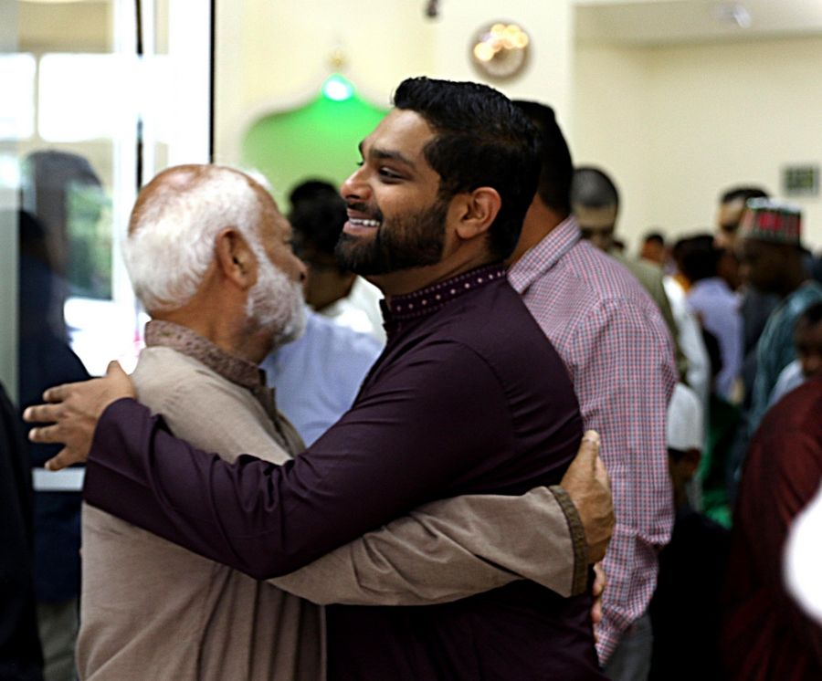 Umair Ahmad Chaudhry of Vernon Hills, right, congratulates his father, Abdus Sattar Chaudhry, upon the conclusion of prayers Sunday morning in celebration of Eid al-Adha at Islamic Foundation North in Libertyville. A sermon was given by Sheikh Farid Fahmy.
