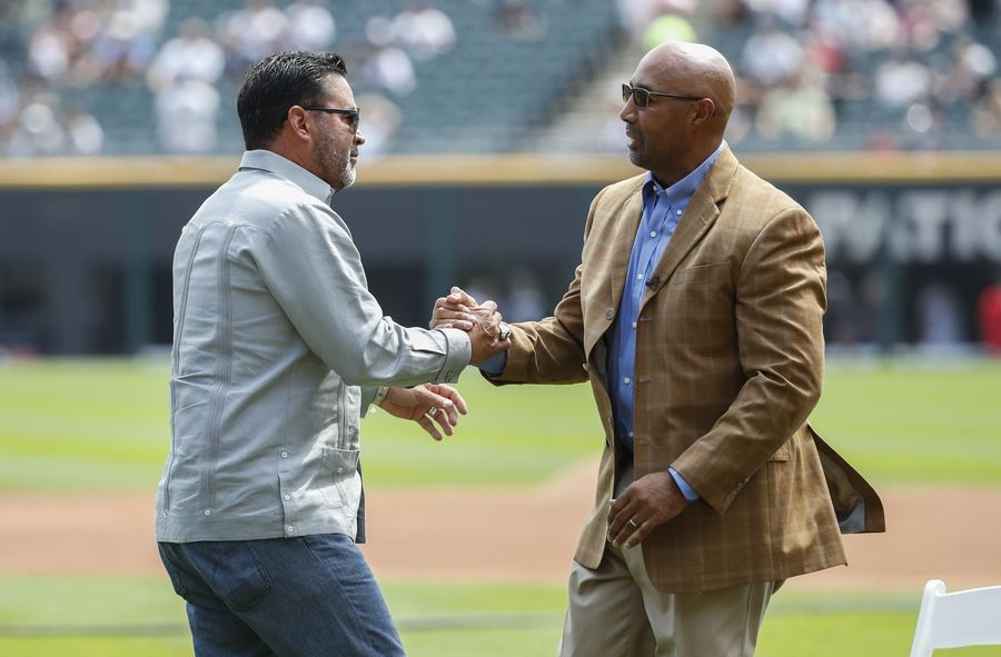 Former Chicago White Sox player Harold Baines, right, shakes hands with former player and manager Ozzie Guillen, left, as he is honored during a ceremony reflecting his Hall of Fame induction before a baseball game between the Chicago White Sox and the Oakland Athletics, Sunday, Aug. 11, 2019, in Chicago.