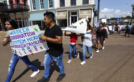 Children of mainly Latino immigrant parents hold signs in support of them and those individuals picked up during an immigration raid at a food processing plant in Canton, Miss., following a Spanish Mass at Sacred Heart Catholic Church in Canton, Miss., Sunday, Aug. 11, 2019. The raids Tuesday at poultry plants in Mississippi have spurred churches that have been key to providing spiritual and emotional comfort to workers to now step up to provide material aid to jailed or out-of-work church members.