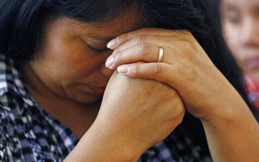 A woman prays during a Spanish Mass at Sacred Heart Catholic Church in Canton, Miss., Sunday, Aug. 11, 2019. Churches have been key to providing spiritual and emotional comfort to workers following immigration raids at seven Mississippi poultry plants, and are now stepping up to provide material aid to jailed or out-of-work church members, even as some church leaders denounce the raids that Republican leaders of the conservative state have applauded.