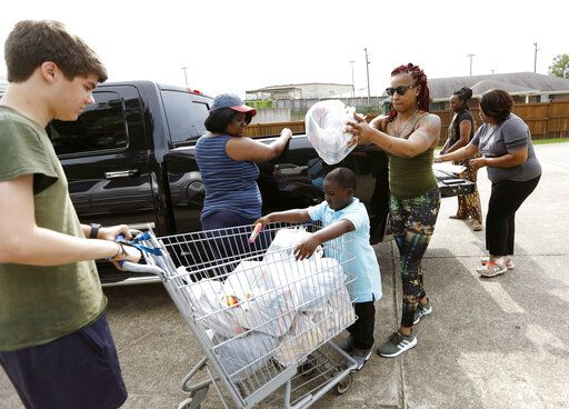 In this Thursday, Aug. 8, 2019 photo, Jesse Van Fleet, left, assists Jasmine Ward and Myles Wright, 5, of Jackson, unload donated items for the pantry at the Carlisle Crisis Center in Forest, Miss. The center, a ministry of Scott County Baptist Association, says they will need more food items to help out the families affected by the fallout of Wednesday's raid by U.S. immigration officials at poultry plants Koch Foods and PH Foods in neighboring Morton. The raids were part of a large-scale operation targeting owners as well as undocumented employees.