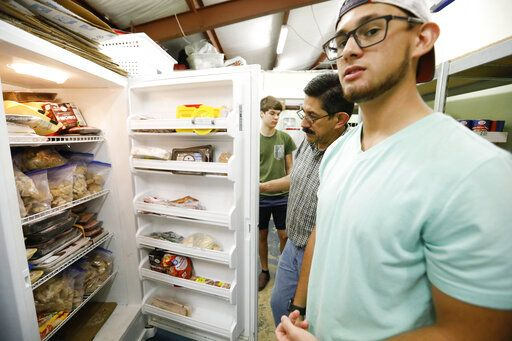 In this Thursday, Aug. 8, 2019 photo, while his father, Pastor Hugo Villegas inspects the freezer, Pablo Villegas, right, says the pantry at the Carlisle Crisis Center in Forest, Miss., has a limited amount of perishable foods, courtesy of the immediate community, as well as contributions from individuals as far away as Jackson, and help from some social agencies and civic groups.  The center, a ministry of Scott County Baptist Association, says they will need more food items to help out the families affected by the fallout of Wednesday's raid by U.S. immigration officials at poultry plants Koch Foods and PH Foods in neighboring Morton. The raids were part of a large-scale operation targeting owners as well as undocumented employees.