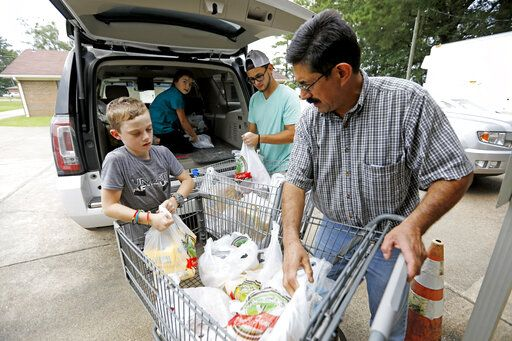 In this Thursday, Aug. 8, 2019 photo, Pastor Hugo Villegas, right, and his son Pablo Villegas, second from right, assist Cade Vowell, left, and his sister Addison Vowell, second from left, unload donated items for the pantry at the Carlisle Crisis Center in Forest, Miss. The center, a ministry of Scott County Baptist Association, says they will need more food items to help out the families affected by the fallout of Wednesday's raid by U.S. immigration officials at poultry plants Koch Foods and PH Foods in neighboring Morton. The raids were part of a large-scale operation targeting owners as well as undocumented employees.