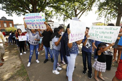 Children of mainly Latino immigrant parents hold signs in support of them and those individuals picked up during an immigration raid at a food processing plant, during a protest march to the Madison County Courthouse in Canton, Miss., following a Spanish Mass at Sacred Heart Catholic Church in Canton on Sunday, Aug. 11, 2019. The raids Tuesday at poultry plants in Mississippi have spurred churches that have been key to providing spiritual and emotional comfort to workers to now step up to provide material aid to jailed or out-of-work church members.