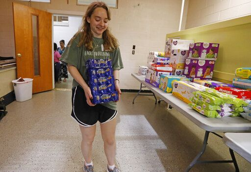 Sacred Heart Catholic Church parishioner Helen Greene carries cans of sausages to a storage room at the old school formerly used by the church, Friday, Aug. 9. 2019 in Canton, Miss. Rice, beans, canned meats, diapers and other sundry items are being collected to assist families affected by the immigration raids of several food processing plants, including one in Canton.