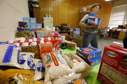 Rice, beans, canned meats, diapers and other sundry items are being stored by Sacred Heart Catholic Church parishioner Mary Greene at the church's old school in Canton, Miss., Friday, Aug. 9, 2019. The items were donated by parishioners, area residents and others to assist families affected by the immigration raids of several food processing plants, including one in Canton.