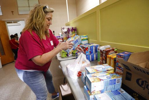 St. Joseph Catholic Church parishioner Gayle Price of Madison, stacks boxes of crackers in a storage room at the old school formerly used by Sacred Heart Catholic Church, Friday, Aug. 9. 2019 in Canton, Miss. Rice, beans, canned meats, diapers and other sundry items are being collected to assist families affected by the immigration raids of several food processing plants, including one in Canton.