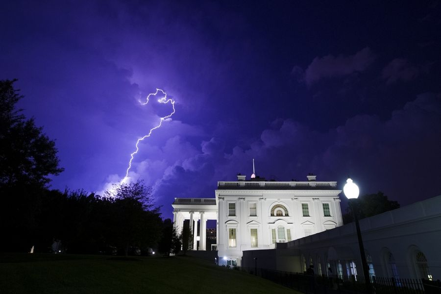 A bolt of lightning illuminates the clouds of a thunderstorm Tuesday behind the White House in Washington.