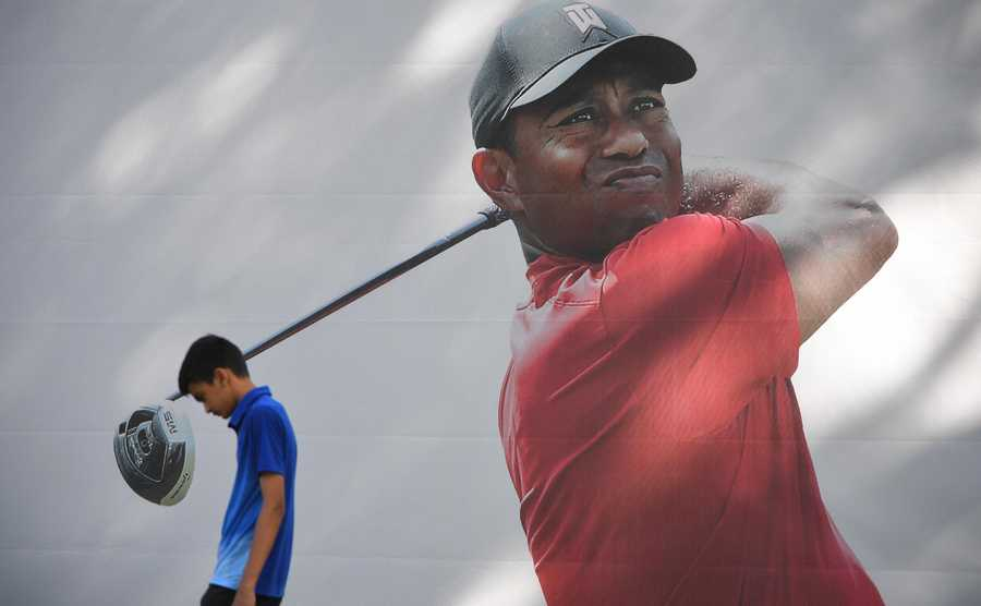 A boy walks past a large mural of Tiger Woods at the BMW Championship practice rounds at Medinah Country Club in Medinah Tuesday.