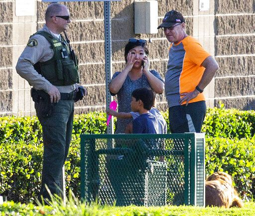 A mother and her two children and the man with his dog that got them away from the scene stand with a deputy not too far from where a shootout by a freeway killed a California Highway Patrol officer and wounded two others before the gunman was fatally shot, Monday, Aug. 12, 2019, in Riverside, Calif. (Terry Pierson/The Orange County Register via AP)