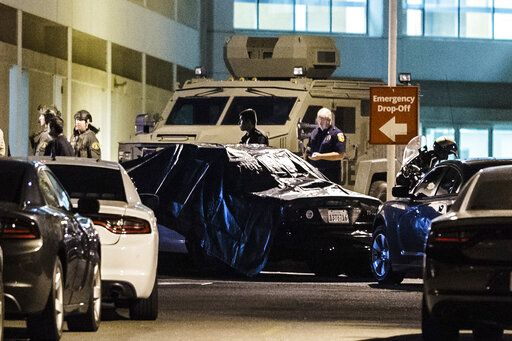 A California Highway Patrol vehicle is covered with a tarp outside the emergency room entrance to the Riverside University Health System Medical Center in Moreno Valley after an officer was killed in a shootout following a traffic stop in Riverside on Monday, Aug 12, 2019. (Watchara Phomicinda/The Orange County Register via AP)