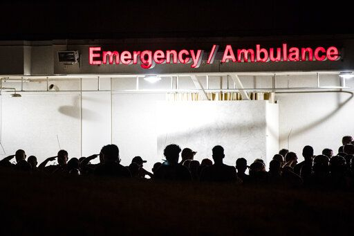 California Highway Patrol Officers gather outside the emergency room entrance to the Riverside University Health System Medical Center in Moreno Valley, Calif., on Monday, Aug 12, 2019 after an officer was killed in a shootout following a traffic stop in Riverside. (Watchara Phomicinda/The Orange County Register via AP)