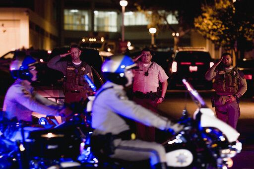 Sheriff deputies salute as California Highway Patrol motorcycle officers lead the procession for a fallen California Highway Patrol officer at Riverside University Health System Medical Center in Moreno Valley, Calif., on Monday, Aug 12, 2019. Moye was killed during a shootout following a traffic stop in Riverside.  (Watchara Phomicinda/The Orange County Register via AP)