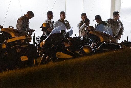 California Highway Patrol officers stage outside an emergency room entrance, late Monday, Aug. 12, 2019, in Moreno Valley, Calif., after a CHP officer was fatally shot during a traffic stop in Riverside. (Gina Ferazzi/Los Angeles Times via AP)