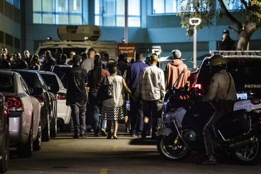 Family members and law enforcement agencies gather outside the emergency room entrance to the Riverside University Health System Medical Center in Moreno Valley after an officer was killed in a shootout following a traffic stop in Riverside on Monday, Aug 12, 2019.  (Watchara Phomicinda/The Orange County Register via AP)
