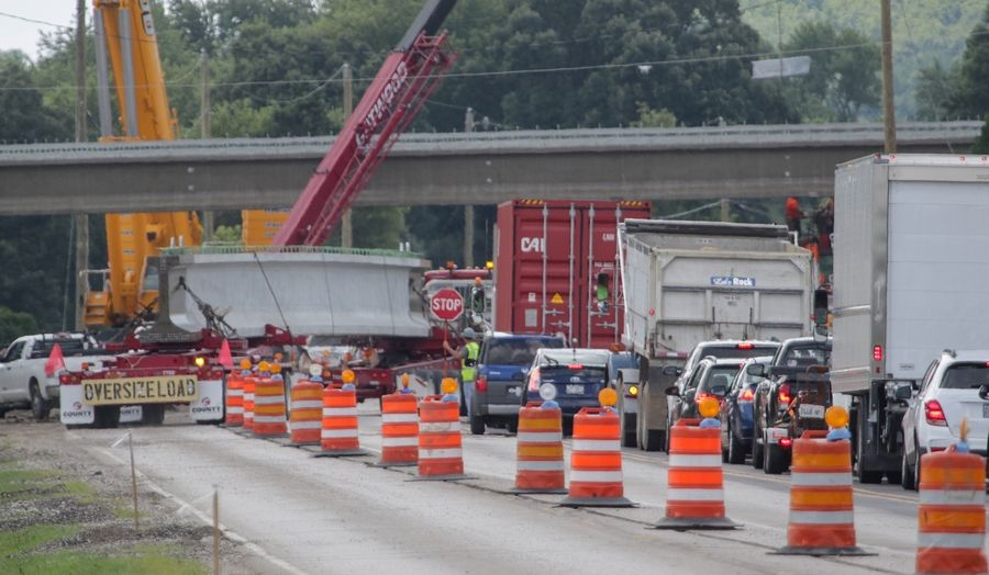 Traffic is stopped along Route 31 as a bridge beam is delivered and off loaded for Longmeadow Parkway construction.
