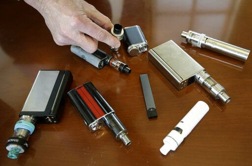 FILE - In this Tuesday, April 10, 2018 photo, a high school principal displays vaping devices that were confiscated from students at the school in Massachusetts. On Wednesday, Aug. 14, 2019, the Vapor Technology Association filed a lawsuit against the U.S. government to delay a review of electronic cigarettes.