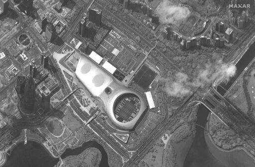 This satellite image captured on Monday, Aug. 12, 2019, provided by Satellite image ©2019 Maxar Technologies appears to show Chinese security force vehicles inside the Shenzen Bay Sports Center, middle, in the southern Chinese city of Shenzhen, bordering Hong Kong. (Satellite image ©2019 Maxar Technologies via AP)