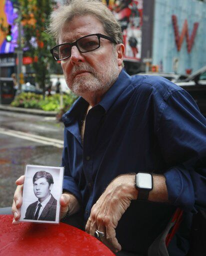 This Wednesday, Aug. 7, 2019 photo shows Brian Toale, holding a photo of himself at 16 years old in New York. Thousands of people who say they were molested as children in New York state will head to court this week to file lawsuits against their alleged abusers and the institutions where they worked.  Toale, 66, who says he was molested by an employee at a Catholic high school he attended on Long Island, was one of the leaders in the fight to pass the Child Victims Act.
