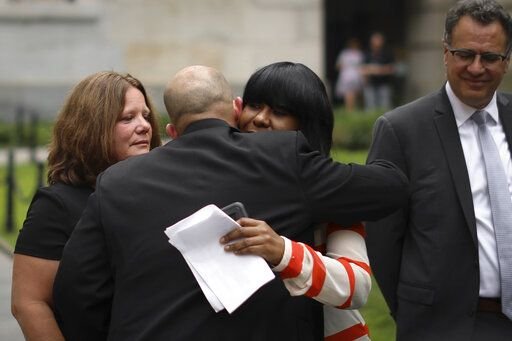Auset Love hugs her attorney after speaking at a news conference outside the New York City Department of Education headquarters on Wednesday, Aug. 14, 2019 in New York. Following the implementation of the New York Child Victims Act, Love filed a lawsuit alleging she was physically and sexually abused by a teacher in New York City starting at the age of nine. At left is Joanne Schoonmaker, who spoke at the news conference after filing a lawsuit under the New York Child Victims Act.