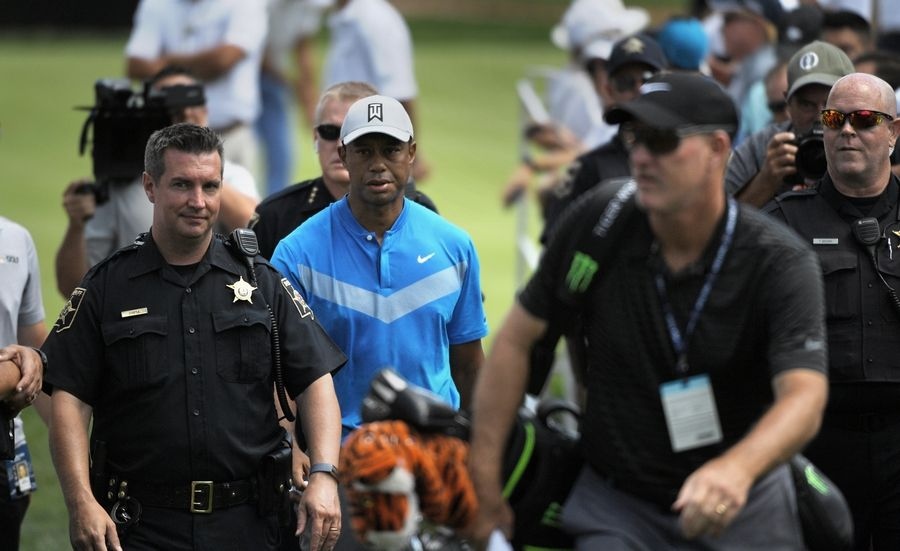 Tiger Woods heads toward the first tee with a DuPage County Sheriff's security detail during the opening round of the BMW Championship at Medinah.