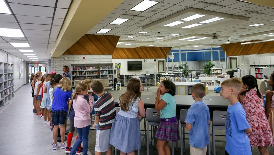 Students line up for a first glimpse of the new learning commons Thursday on their first day of school at Scott Elementary in Naperville Unit District 203.