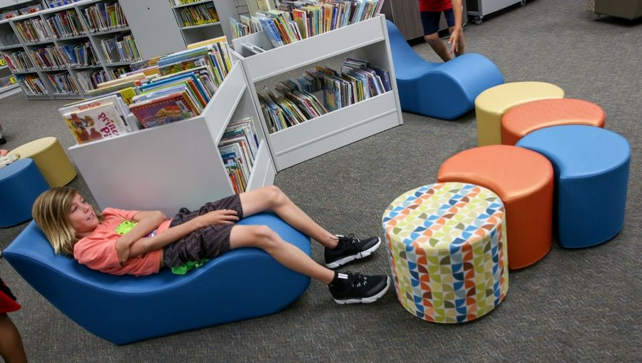 Christian Hay lounges for a moment on new furniture in a renovated learning commons Thursday during his first day of fifth grade at Scott Elementary in Naperville Unit District 203.