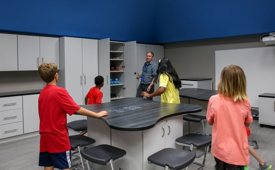 Learning commons director and teacher Scott Larson shows kids a new classroom Thursday on the first day of school at Scott Elementary in Naperville Unit District 203.