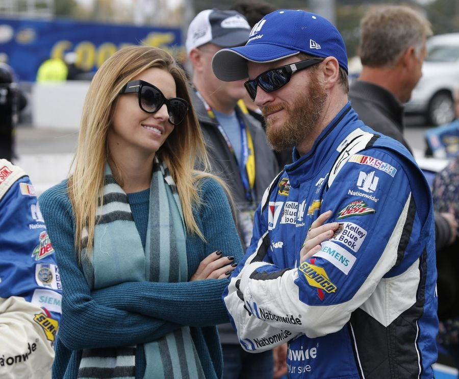 In this Sunday, Nov. 1, 2015 file photo, Sprint Cup Series driver Dale Earnhardt Jr. (88) talks with his fiance, Amy Reimann, prior to the Sprint Cup auto race at Martinsville Speedway in Martinsville, Va. NASCAR television analyst and former driver Dale Earnhardt Jr. was taken to a hospital after his plane crashed in east Tennessee.