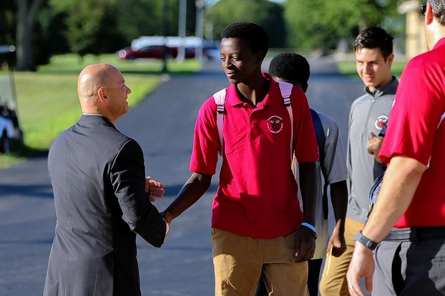 Mooseheart Executive Director Gary Urwiler, left, greets freshman Heritier Rukumbuzi on Thursday, the opening day of the school year.