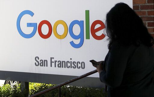 FILE - In this May 1, 2019, file photo, a person walks past a Google sign in San Francisco. Google employees are calling on the company to pledge it won't work with U.S. Customs and Border Protection or Immigration and Customs Enforcement _ the latest in a year full of political and social pushback from the tech giant's workforce.