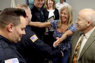 Sharon, center, and Christopher Loeber, right, offer hugs for Long Grove Fire Protection District firefighters and a nurse honored Monday night for springing to action to save his life after he drove up to the station seeking help on July 16. He was saved after going into cardiac arrest. From left, firefighters William Eisner, Tyler Gates, and Jake Gross, registered nurse Elizabeth Keane and Battalion Chief John Jaworski