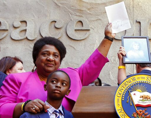 Assemblywoman Shirley Weber, D-San Diego, holds up her measure signed by Gov. Gavin Newsom that limits the use of lethal force by law enforcement Sacramento, Calif., Monday, Aug. 19, 2019. Weber's bill, AB392, would bar police from using lethal force unless it is necessary to prevent imminent threat of death or serious injury to themselves and others.