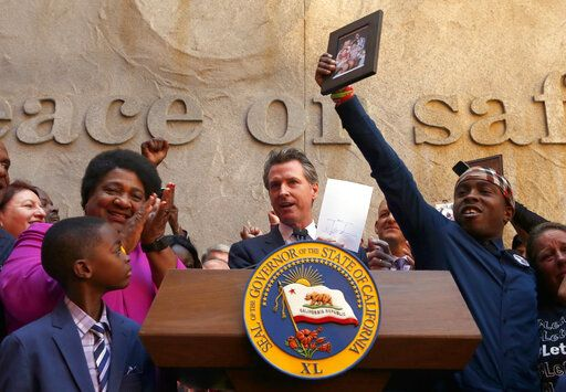 Gov. Gavin Newsom holds up the measure by Assemblywoman Shirley Weber, D-San Diego, left, that he signed that limits the use of lethal force by law enforcement Sacramento, Calif., Monday, Aug. 19, 2019. Weber's bill, AB392, would bar police from using lethal force unless it is necessary to prevent imminent threat of death or serious injury to themselves and others. Stevante Clark, right, holds up a photo of his brother, Stephon Clark, who was shot and killed by Sacramento Police in 2018.