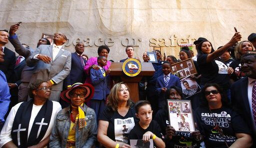 Supporters of a bill limiting the police use of deadly force surround Gov. Gavin Newsom, center, during a signing ceremony in Sacramento, Calif., Monday, Aug. 19, 2019. California is changing its standards for when police can kill under a law signed Monday by Newsom, as it tries to deter police shootings of young minority men that have roiled the nation.
