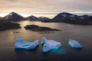 Large Icebergs float away as the sun rises near Kulusuk, Greenland. Scientists are hard at work, trying to understand the alarmingly rapid melting of the ice.