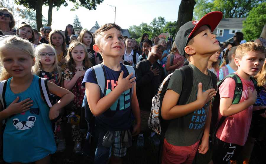 Wynn Thomas, 6, and Vuk Vuckovic, 6, both first graders say the Pledge of Allegiance on their first day back to school at Rockland School in Libertyville on Wednesday.