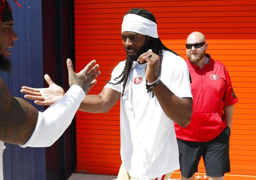 San Francisco 49ers cornerback Richard Sherman, right, greets middle linebacker Kwon Alexander as he heads up to the podium to speak to reporters after a combined NFL football training camp with the Denver Broncos at the Broncos' headquarters Friday, Aug. 16, 2019, in Englewood, Colo.