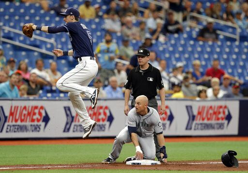 Seattle Mariners' Kyle Seager, lower right, slides into third base safely as Tampa Bay Rays' Matt Duffy fields a wild throw on a single by Omar Narvaez during the fourth inning of a baseball game Wednesday, Aug. 21, 2019, in St. Petersburg, Fla. Looking on is umpire D.J. Reyburn.