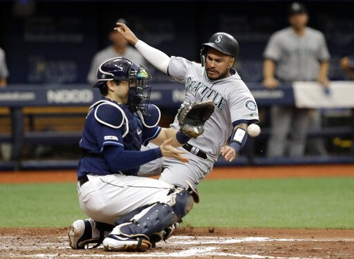 Seattle Mariners' Omar Narvaez, right, scores ahead of the throw to Tampa Bay Rays catcher Travis d'Arnaud on a two-run single by Tim Lopes during the fourth inning of a baseball game Wednesday, Aug. 21, 2019, in St. Petersburg, Fla.