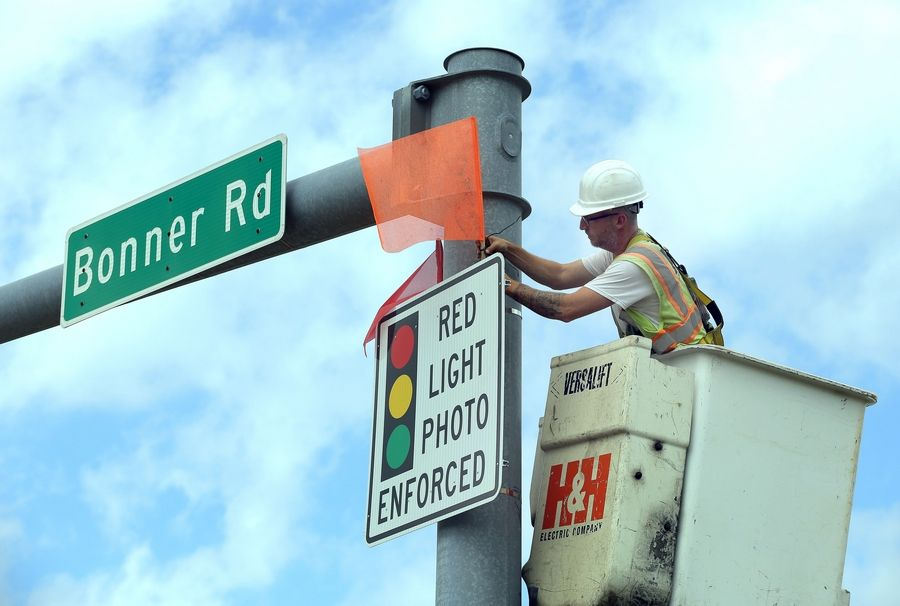 Chris Bachewicz of H & H Electric puts flags on a sign alerting drivers to a red-light camera at the corner of Bonner  Road and Route 12 in Wauconda.