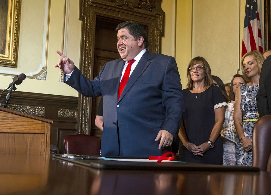 Illinois Governor J.B. Pritzker answers questions Thursday from the media after signing legislation raising the minimum salary for teachers to $40,000 in the Governor's office at the Illinois State Capitol.