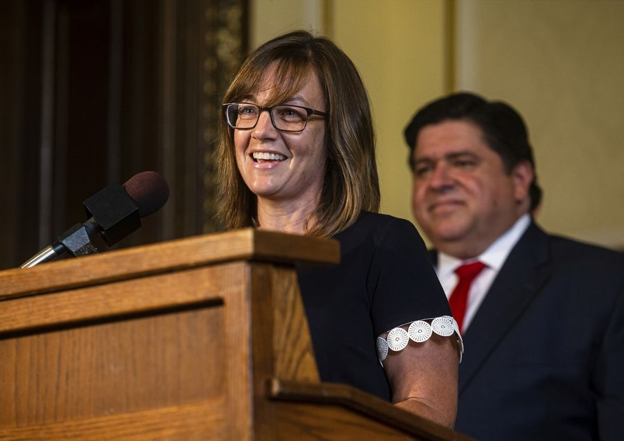 Illinois State Rep. Katie Stuart, D-Collinsville, speaks Thursday to the benefits to teachers in the bill she sponsored that would raise the minimum salary for teachers to $40,000 prior to Illinois Governor J.B. Pritzker, right, singing the bill in his office at the Illinois State Capitol.